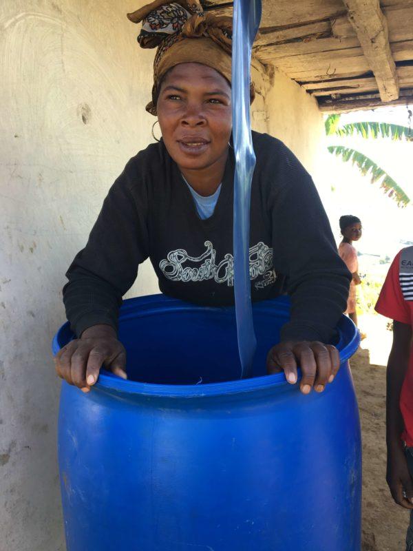 Haitian woman holding water bucket