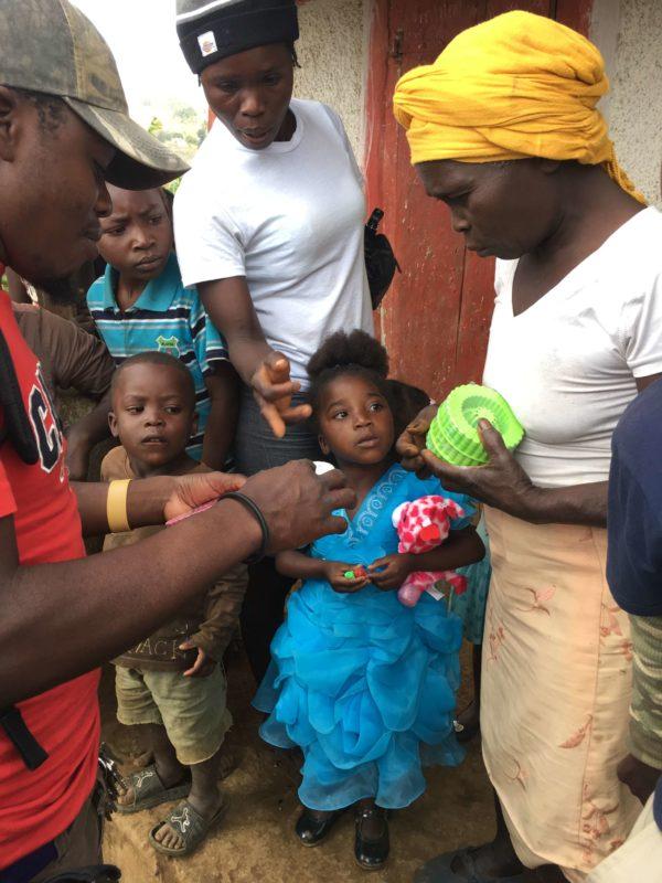 giving children's tespo pods to moms in haiti